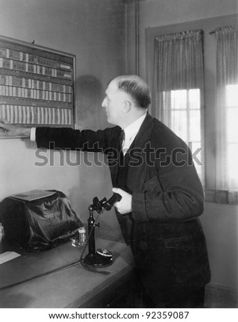 Man in his office looking at a board - stock photo