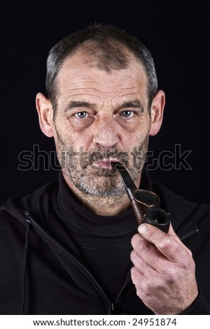 Man in his sixties smoking a pipe - stock photo