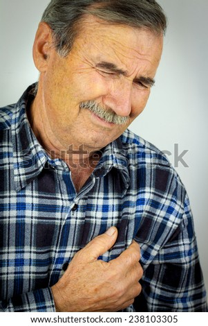 Man in his sixties suffering pain from a heart attack - stock photo
