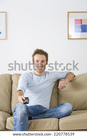 Man in his twenties on sofa with TV remote control - stock photo