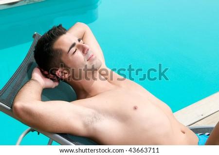 man in holidays having a sun bath near a swimming pool - stock photo