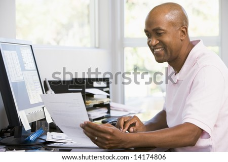 Man in home office using computer and smiling - stock photo