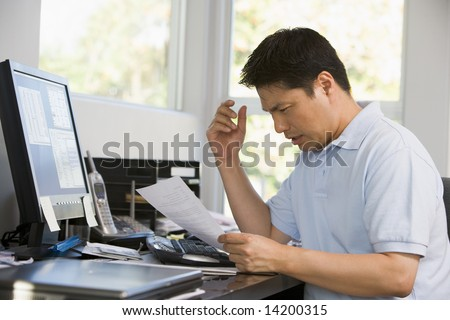 Man in home office with computer and paperwork frustrated - stock photo
