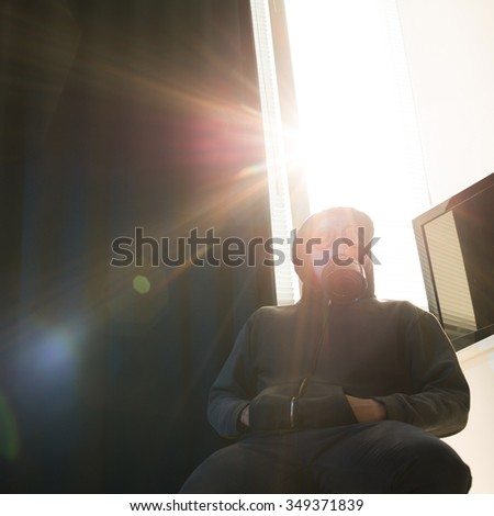 Man in hood and respirator sitting at wall - stock photo