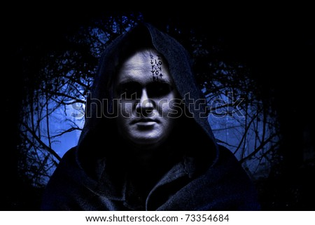 Man in hood on the spooky forest background. - stock photo