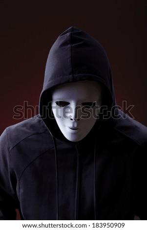 Man in hood wearing mask over dark background - stock photo