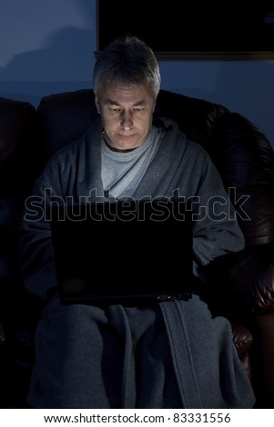 Man in housecoat working late series serious - stock photo