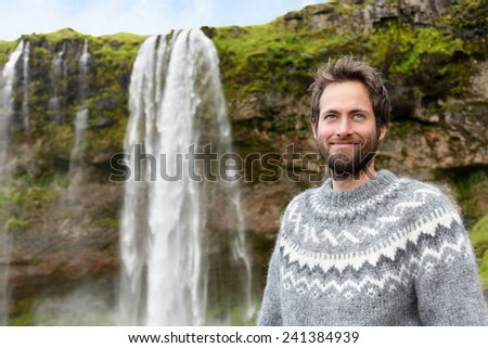 Man in Icelandic sweater by waterfall on Iceland. Bearded male portrait of good looking guy in his 30s in nature landscape with tourist attraction Seljalandsfoss waterfall on Ring Road. - stock photo