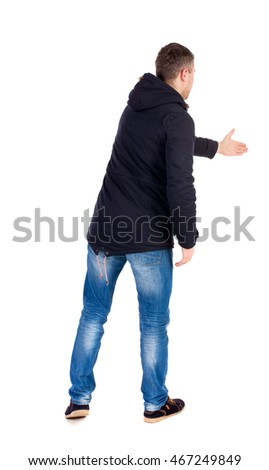 man in jacket holds out his hand for handshake. Rear view  people collection.  backside view of person.  Isolated over white background. A guy in a black jacket holding out his hand in greeting.