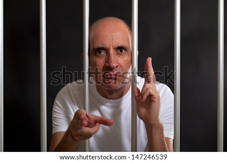 Man in jail gesturing guns with his hands - stock photo