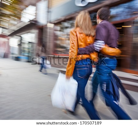 Man in jeans and a woman in a leather jacket walking down the street hugging. Intentional motion blur - stock photo