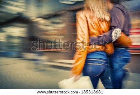 Man in jeans and a woman in a leather jacket walking down the street hugging. Intentional motion blur and color shift - stock photo