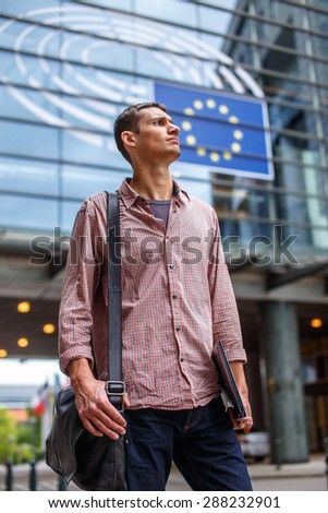 Man in jeans and red shirt on the city street. - stock photo