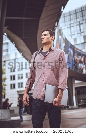 Man in jeans and red shirt with laptop in hand walking on the city street. - stock photo