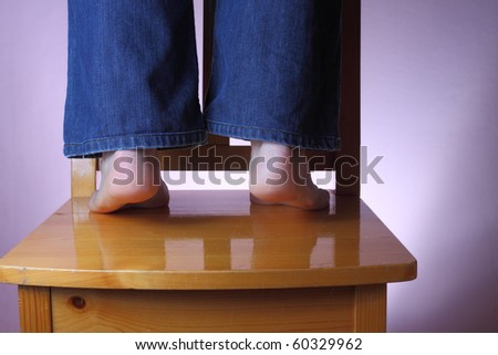 Man in jeans standing barefoot on wooden chair, keeping on his toes