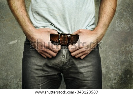 Man in jeans with fashionable leather belt - stock photo