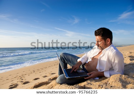 man in jeans working in a laptop at the beach