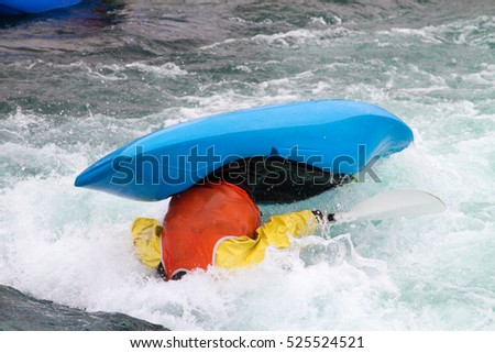 Man in kayak being capsized and over turned by the fast rushing water
