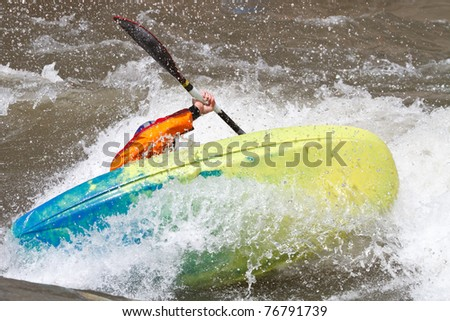 man in kayak fighting rapids of a river