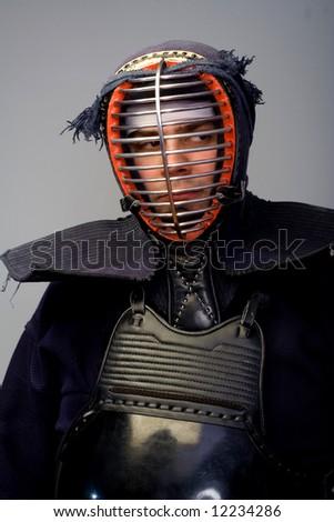 Man in kendo helmet with eyes looking on side - stock photo