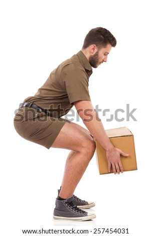 Man in khaki uniform picking up a carton box, side view. Full length studio shot isolated on white. - stock photo