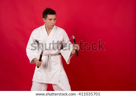 Man in kimono practicing martial arts. Master display nunchaku kata.  - stock photo