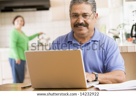 Man in kitchen with laptop smiling with woman in background - stock photo
