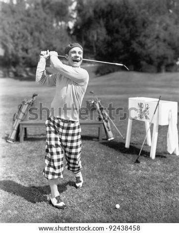 Man in knickerbockers swinging a golf club - stock photo