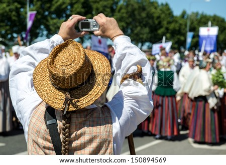 Man in latvian national costume take a photo. Photo taken in Latvian National Song and Dance Festival - stock photo
