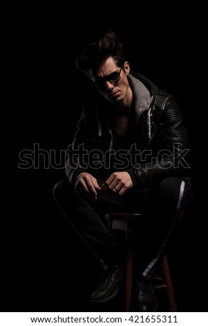 man in leather jacket and boots wearing sunglasses sitting on a chair in studio