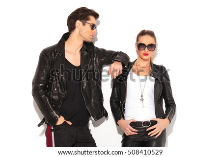 man in leather jacket leaning elbow on girlfriend's shoulder on white studio wall