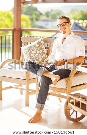 man in light interior relaxing with cup of coffee or tea