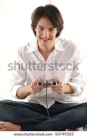 Man in living room playing hand-held video-game smiling - stock photo