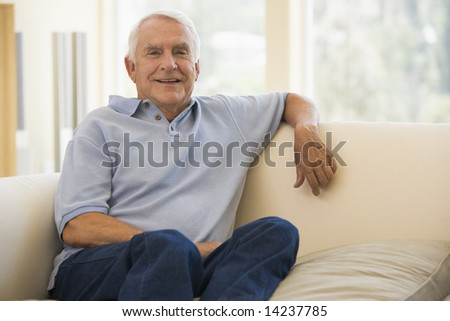 Man in living room smiling - stock photo