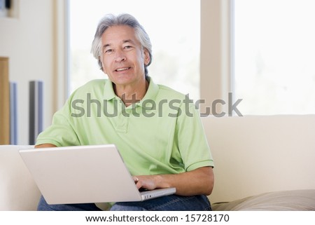 Man in living room with laptop smiling - stock photo