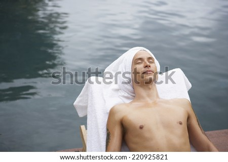 Man in lounge chair next to water - stock photo