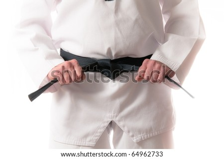 Man in martial arts uniform holding his black belt with both hands - stock photo