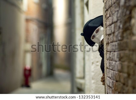 Man in mask looking around the corner, on Venice street - stock photo