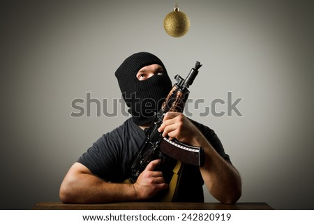 Man in mask with gun and Christmas ball which is above his head. Waiting of Christmas and New Year. - stock photo
