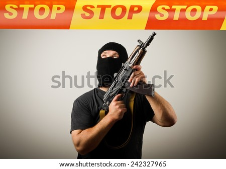 Man in mask with gun and STOP line over his head. Restricted area concept. - stock photo