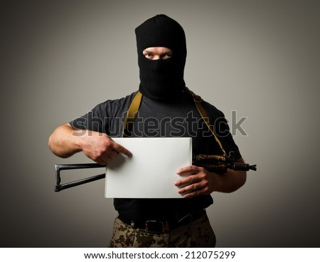 Man in mask with gun is holding white paper.