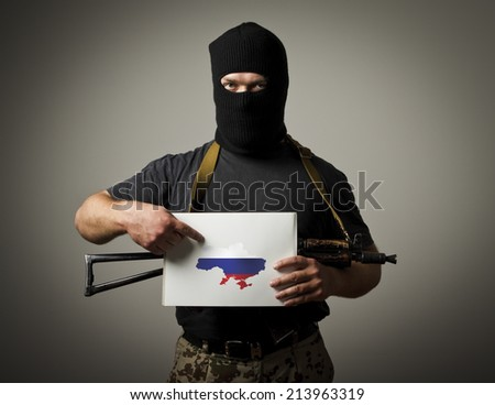 Man in mask with gun is holding white paper with a map of Ukraine.