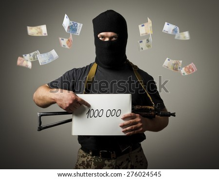 Man in mask with gun is holding white paper with a sign. Ransom, tribute and racketeering concept. - stock photo