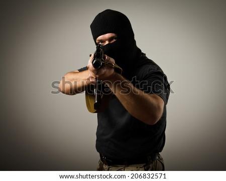 Man in mask with gun. Russian terrorist. - stock photo