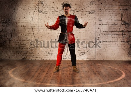 Man in medieval suit performing magic moment - stock photo