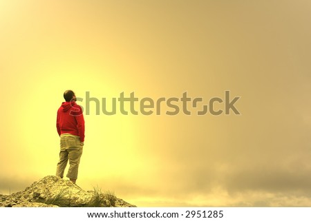 man in meditation on top of the mountain at sunset - stock photo