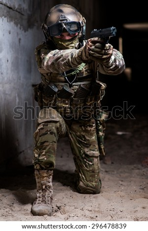 Man in military ammunition stay on his knees with gun in hand - stock photo