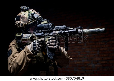 man in military uniform with assault rifle aiming at target on background of dark wall/Soldier in gas mask with rifle in hands - stock photo