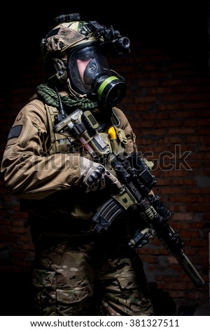Man in military uniform with mask, helmet and rifle on dark wall background looking at camera/Soldier with rifle and respirator on dark background