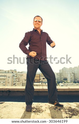 Man in modern sunglasses dancing with joy. Happy man! Good mood in men. Red haired man standing against the sky. Hello Friend! It dances on the roof. - stock photo
